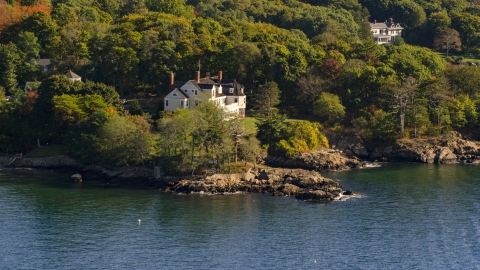 AX147_055.0000017 - Aerial stock photo of An oceanfront mansion among trees, autumn, Beverly, Massachusetts