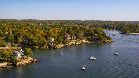 AX147_060.0000221 - Aerial stock photo of Oceanfront homes and trees with fall leaves, autumn, Manchester-by-the-Sea, Massachusetts
