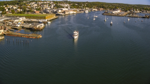 AX147_088.0000030 - Aerial stock photo of A ferry by a small coastal town, Gloucester, Massachusetts