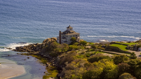 AX147_107.0000030 - Aerial stock photo of Oceanfront home on rocky shoreline, Gloucester, Massachusetts