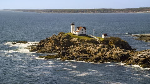 AX147_238.0000000 - Aerial stock photo of Cape Neddick Light, coastal town in background in autumn, York, Maine