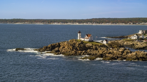 AX147_238.0000188 - Aerial stock photo of Cape Neddick Light, coastal town in background, autumn, York, Maine