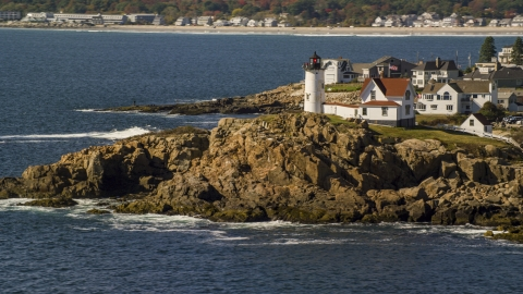 AX147_239.0000000 - Aerial stock photo of Cape Neddick Light on a rocky shore, autumn, York, Maine