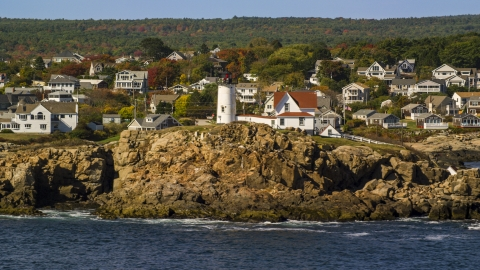 AX147_239.0000259 - Aerial stock photo of Cape Neddick Light, town behind it, autumn, York, Maine