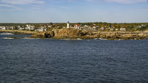 AX147_240.0000000 - Aerial stock photo of The Cape Neddick Light with the town behind it in autumn, York, Maine