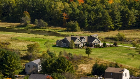 AX147_290.0000049 - Aerial stock photo of A riverfront rural home near forest, Biddeford, Maine