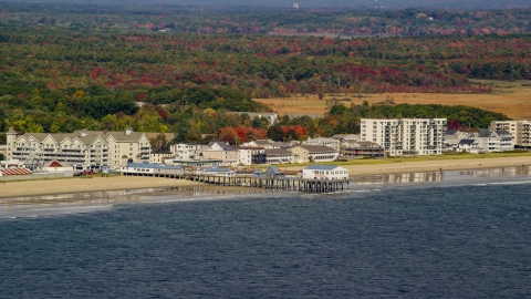 AX147_295.0000000 - Aerial stock photo of A beach and pier by colorful autumn trees, Old Orchard Beach, Maine