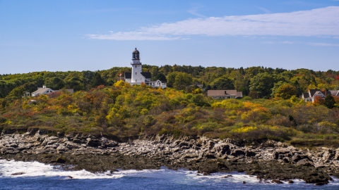 AX147_306.0000287 - Aerial stock photo of Cape Elizabeth Light seen from the rocky shore, autumn, Cape Elizabeth, Maine