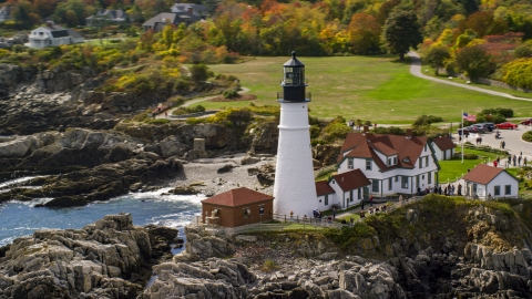 AX147_313.0000047 - Aerial stock photo of Portland Head Light on the rocky coast near colorful autumn trees, Cape Elizabeth, Maine