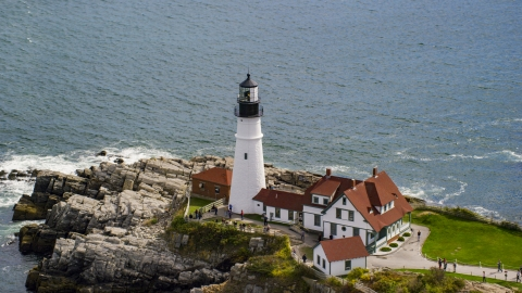 AX147_314.0000147 - Aerial stock photo of Portland Head Light on the edge of a rocky shore, Cape Elizabeth, Maine