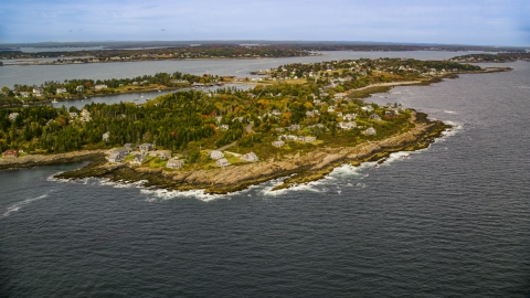 AX147_379.0000071 - Aerial stock photo of A coastal town on Bailey Island with autumn trees, Harpswell, Maine