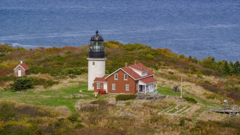 AX147_393.0000263 - Aerial stock photo of Seguin Light on Seguin Island with fall foliage, Phippsburg, Maine