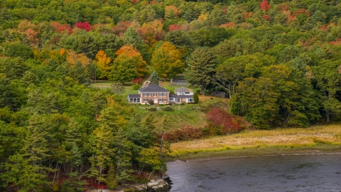 AX147_407.0000000 - Aerial stock photo of An isolated waterfront home, colorful autumn trees, Phippsburg, Maine