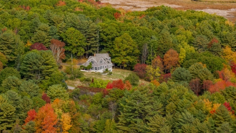 AX147_409.0000000 - Aerial stock photo of An isolated rural home, colorful trees in autumn, Arrowsic, Maine