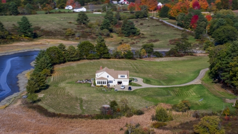 AX148_011.0000112 - Aerial stock photo of An isolated home with green lawn and colorful autumn trees, Newcastle, Maine
