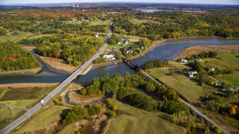 AX148_067.0000079 - Aerial stock photo of Small bridges, Highway 1 over river near rural homes, autumn, Thomaston, Maine