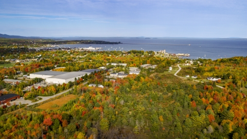 AX148_076.0000028 - Aerial stock photo of A forest near warehouse buildings and small coastal town, autumn, Rockland, Maine
