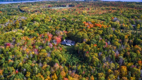 AX148_079.0000017 - Aerial stock photo of A lone rural home and a colorful forest, autumn, Owls Head, Maine