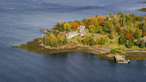 AX148_080.0000035 - Aerial stock photo of Waterfront homes by trees with colorful foliage in autumn, Owls Head, Maine