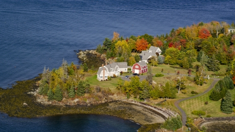 AX148_080.0000159 - Aerial stock photo of Waterfront homes, and colorful foliage on nearby trees in autumn, Owls Head, Maine