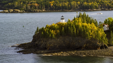 AX148_084.0000022 - Aerial stock photo of Owls Head Light beside the water and trees with fall foliage, autumn, Owls Head, Maine