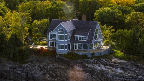 AX148_184.0000221 - Aerial stock photo of A mansion on a rocky shore in autumn, Bar Harbor, Maine