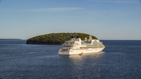 AX148_200.0000250 - Aerial stock photo of A cruise ship sailing past a tiny island, Bar Harbor, Maine