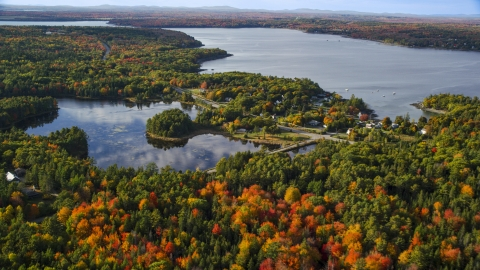 AX148_230.0000028 - Aerial stock photo of Fall foliage around a pond and coastal town, Bar Harbor, Maine