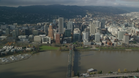 AX153_083.0000281F - Aerial stock photo of Downtown Portland skyscrapers across the Hawthorne Bridge and the Willamette River, Oregon