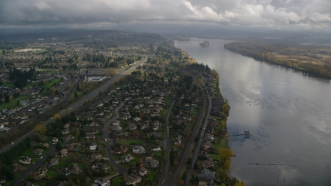 AX153_141.0000277F - Aerial stock photo of Suburban riverfront neighborhoods by Highway 14 in Vancouver, Washington