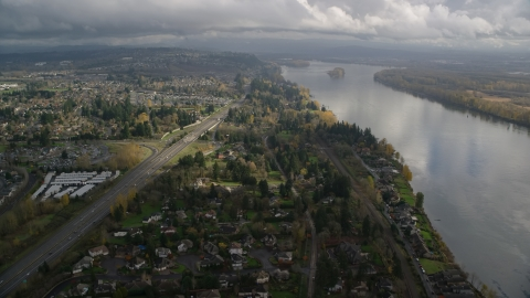 AX153_142.0000206F - Aerial stock photo of Highway 14 and suburban homes on the Columbia River in Vancouver, Washington