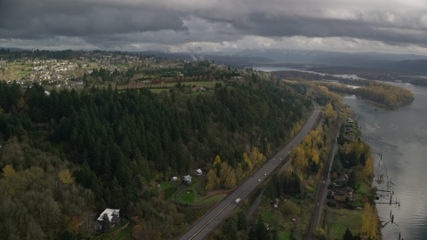 AX153_146.0000208F - Aerial stock photo of High above Highway 14 and hilltop suburban homes, autumn, Camas, Washington