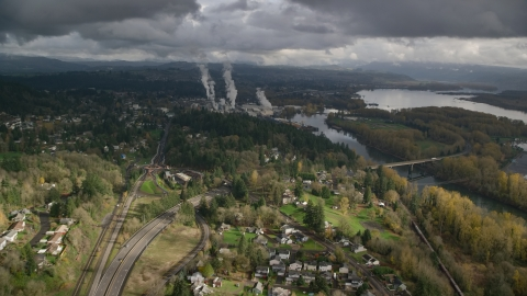 AX153_149.0000054F - Aerial stock photo of High above Highway 14 looking out toward a paper mill in Camas, Washington