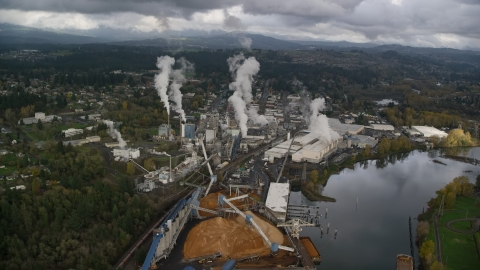 AX153_151.0000293F - Aerial stock photo of Steam rising from the Georgia Pacific Paper Mill in Camas, Washington