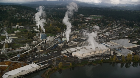 AX153_152.0000265F - Aerial stock photo of Steam rising from the Georgia Pacific Paper Mill in Camas, Washington
