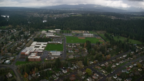 AX153_155.0000018F - Aerial stock photo of School campuses and sports fields in Camas, Washington