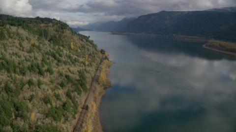 AX154_001.0000000F - Aerial stock photo of Train tracks at the bottom of a cliff in Columbia River Gorge, Oregon