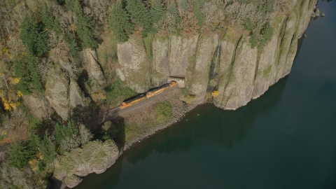 AX154_013.0000254F - Aerial stock photo of A train leaving Cape Horn Railroad Tunnel in Columbia River Gorge, Washington