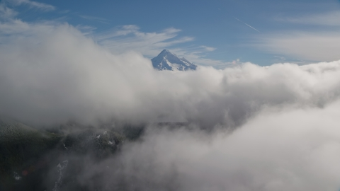 AX154_060.0000000F - Aerial stock photo of Mount Hood, visible above a layer of thick clouds, Cascade Range, Oregon