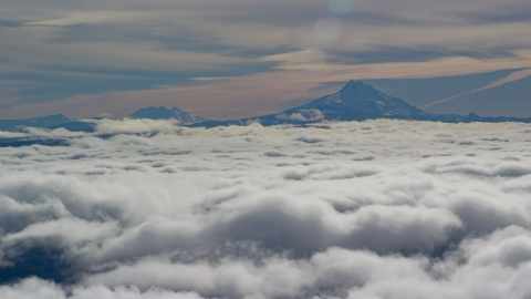 AX154_098.0000218F - Aerial stock photo of Mount Jefferson and the Three Sisters Volcanoes seen from across low clouds, Cascade Range, Oregon