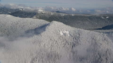 AX154_100.0000000F - Aerial stock photo of A snow covered mountain ridge and forest in the Cascade Range, Oregon