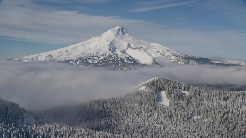 AX154_112.0000000F - Aerial stock photo of Mount Hood behind low clouds and snowy forest in the Cascade Range, Oregon