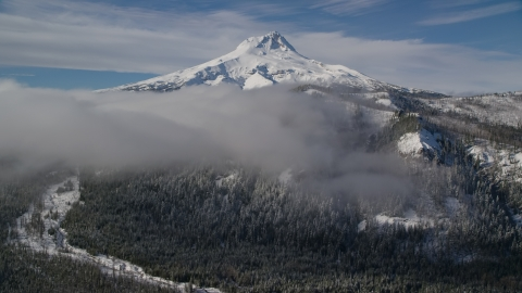 AX154_121.0000120F - Aerial stock photo of Low clouds over forest and ridge near snow-capped Mount Hood, Cascade Range, Oregon