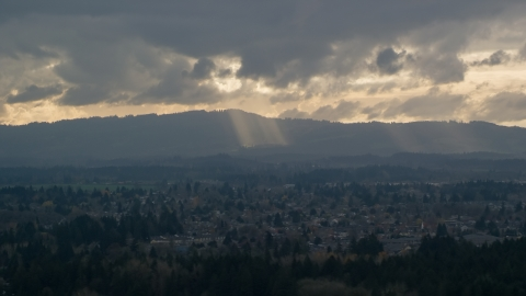 AX155_007.0000000F - Aerial stock photo of Cascade Range and godrays shining from clouds seen from suburban neighborhood, Beaverton, Oregon