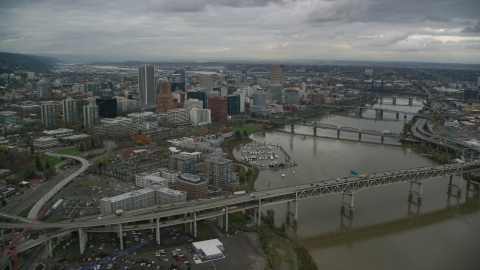 AX155_049.0000308F - Aerial stock photo of Marquam Bridge and Riverplace Marina near skyscrapers in Downtown Portland, Oregon