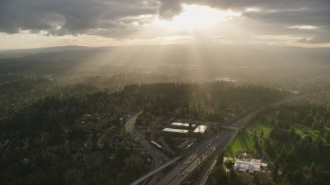 AX155_119.0000000F - Aerial stock photo of Godrays shining down on suburban neighborhoods and Highway 26, Southwest Portland, Oregon