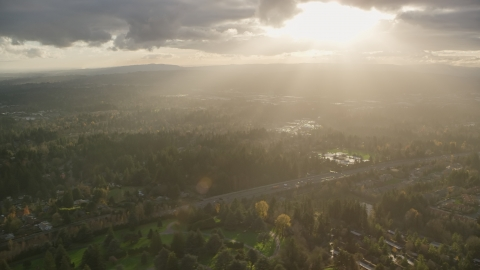 AX155_119.0000265F - Aerial stock photo of Godrays shining down on suburban neighborhoods and Highway 26, Southwest Portland, Oregon