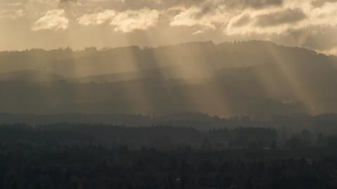 AX155_124.0000225F - Aerial stock photo of Godrays shining down on mountains near Beaverton, Oregon at sunset
