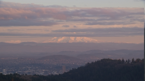 AX155_139.0000222F - Aerial stock photo of Mount Hood and Downtown Portland at sunset, seen from forest and hills in Northwest Portland, Oregon