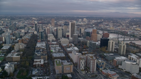 AX155_149.0000211F - Aerial stock photo of Skyscrapers and city streets near the Willamette River at sunset in Downtown Portland, Oregon